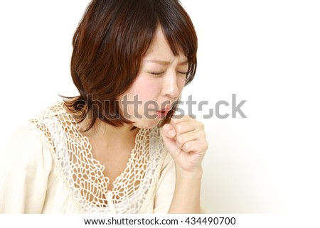 young Japanese woman coughing - stock photo