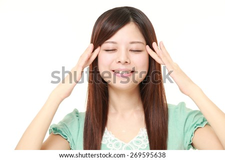 young Japanese woman doing self head massage - stock photo