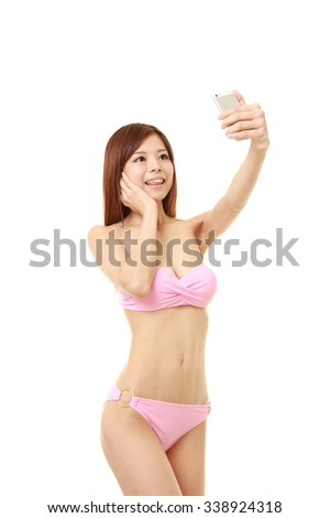 young Japanese woman in a pink bikini takes a selfie - stock photo