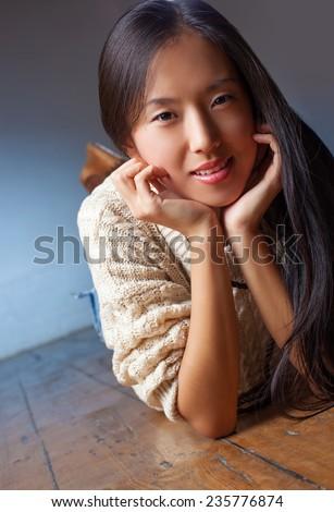 Young japanese woman lying on floor portrait. - stock photo