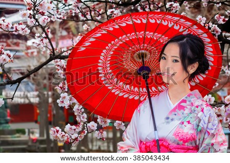 Young Japanese Woman with Sakura - Cherry Blossom in Spring - stock photo