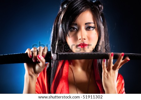 Young japanese woman with samurai sword fashion. Focus on face. - stock photo