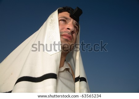 Young jewish man praying on against a clear sky background