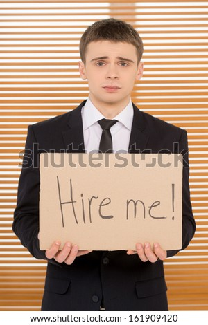 Young jobless man showing plate with sign hire me. Looking sad   - stock photo