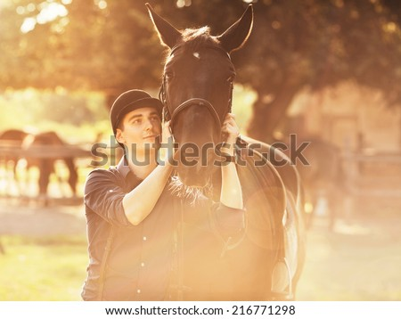 Young jockey preparing his horse for a ride - stock photo