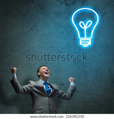 Young joyful businessman screaming with hands up