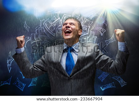 Young joyful businessman with hands up celebrating success - stock photo