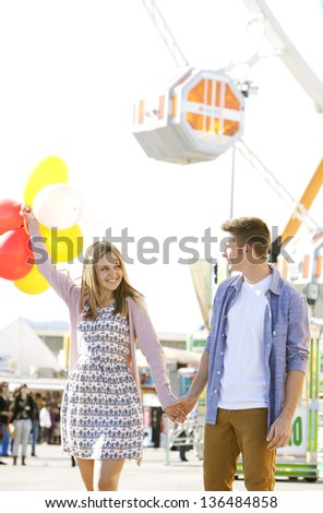 Young joyful couple having fun in a fun fair ground, smiling and holding colorful balloons. - stock photo