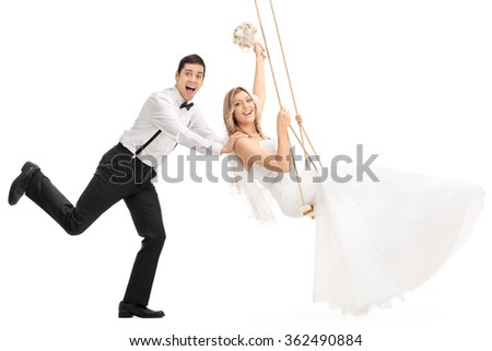 Young joyful man pushing his newlywed wife on a swing isolated on white background - stock photo