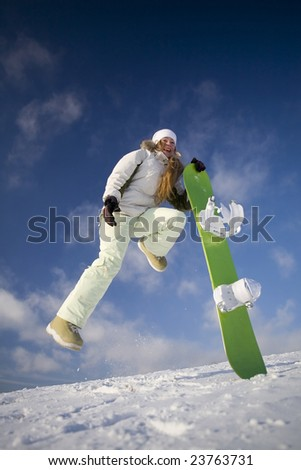 Young joyful snowboarder woman at mountains