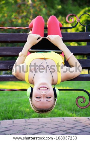 Young joyful woman listening a music in the park with laptop - stock photo