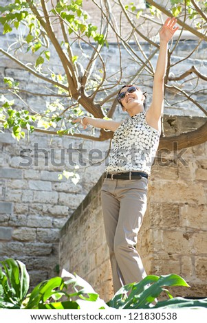 Young joyful woman on vacation standing by a tree with her arms outstretched in the air on a sunny day. - stock photo