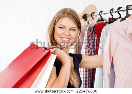 Young joyful woman with colorful shopping bags indoors in retail store. Spree female shopper choosing dress in clothing shop.  - stock photo