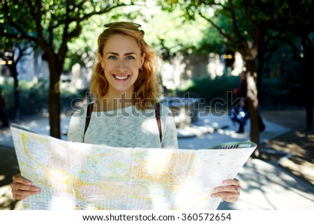 Young joyful woman with tourist map in hands enjoying beautiful strolling during her spring journey, happy female with cute smile studying atlas before walking in foreign city during summer trip - stock photo