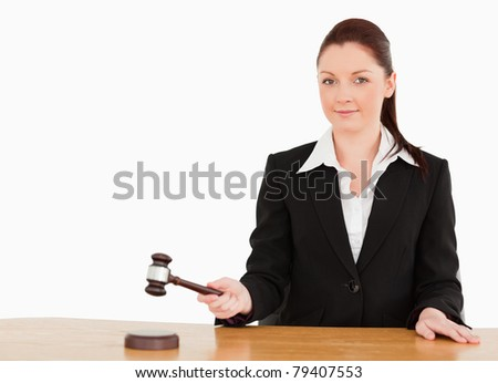 Young judge knocking a gavel smiling at the camera  against a white background