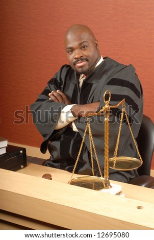 Young judge sitting at his desk with crossed arms and smiling - stock photo