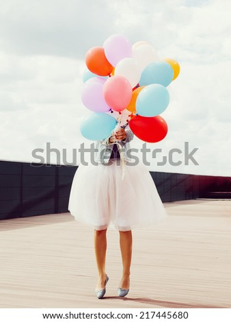 Young jumping girl with colorful balloons in her hands. Warm sunny day. Outside. - stock photo