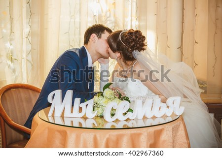 """Young just married couple celebrate their wedding in a cafe, kissing and enjoying each other. At the table standing the inscription in Russian """"We are family"""". - stock photo"""
