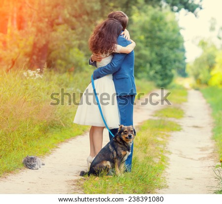 Young just married couple hugging in the forest. Dog and cat sitting near the couple. - stock photo