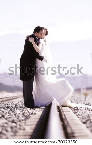 Young just married couple on railway road. - stock photo