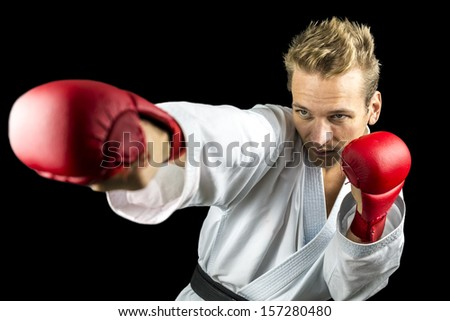 Young K1 fighter punching. Isolated over black background.