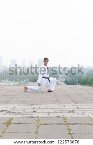 Young karate master doing exercise n the morning on city background