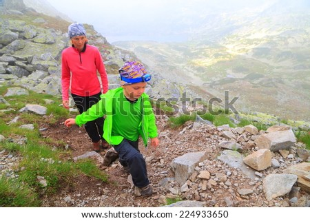 Young kid accompanied by his mother ascending through fog on steep mountain trail - stock photo