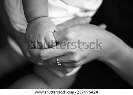Young kid arm in old arm - stock photo
