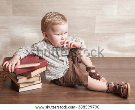 Young Kid boy reading a book on the stack of books. 2 years old Child