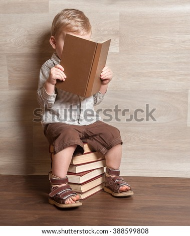 Young Kid boy reading a book on the stack of books. 2 years old Child  - stock photo
