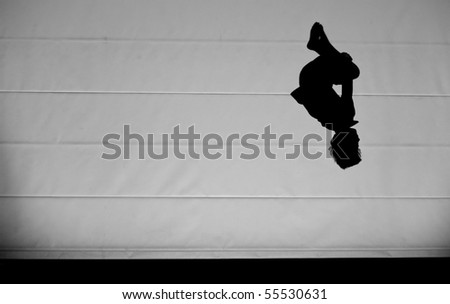 young kid doing a somersault on trampoline in backlight - stock photo