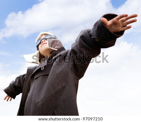 Young kid dreaming of being a pilot looking at the sky - stock photo