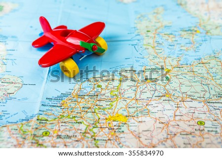 Young kid explorer of the Europe is flying round the world trip on his toy plane. The concept of traveling with children. Toy airplane landed on the map