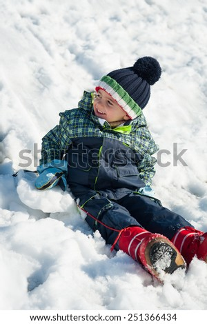 Young kid having fun in the snow. - stock photo