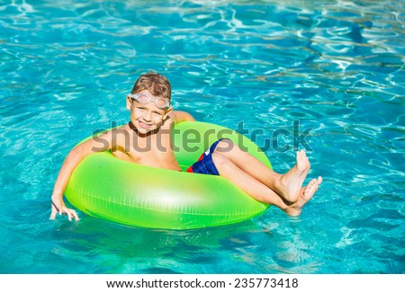 Young Kid Having Fun in the Swimming Pool On Inner Tube Raft. Summer Vacation Fun.  - stock photo