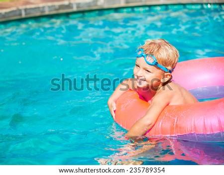 Young Kid Having Fun in the Swimming Pool On Inner Tube Raft. Summer Vacation Fun.  - stock photo