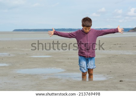 Young kid having fun with quicksand on the beach in front of Mont Saint Michel ancient village. Normandy, France.  - stock photo