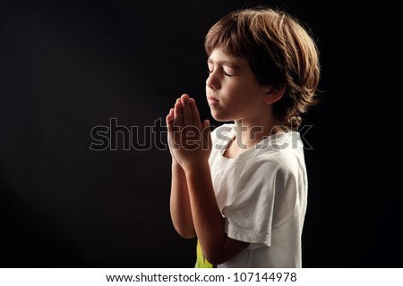 young kid in a spiritual peaceful moment praying - stock photo