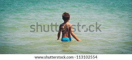 Young kid in the sea. - stock photo