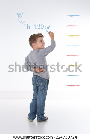 young kid measures his own height on the wall - stock photo