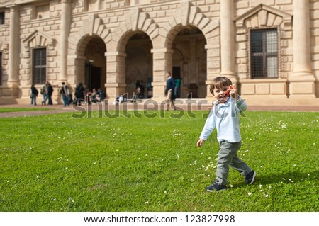 Young kid playing outdoors with toy car. - stock photo