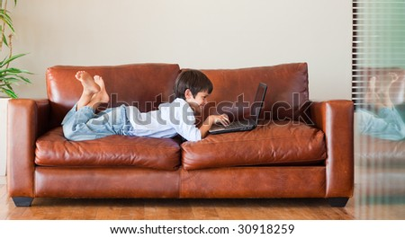 Young kid playing with a laptop on the couch - stock photo