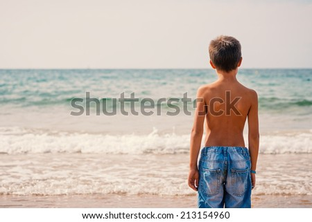 Young kid portrait at the beach looking at the sea.