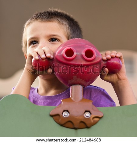 Young kid portrait with binoculars in a playground outdoor.  - stock photo