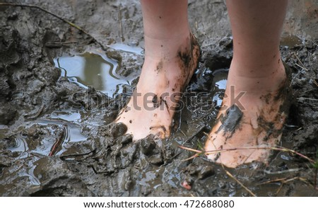 Young kid's muddy feet. Selective focus.