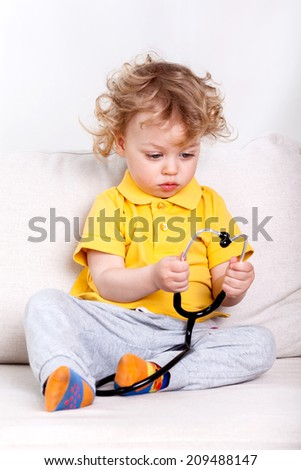 Young kid sitting on a couch and playing with a stethoscope