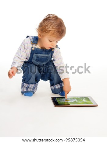 young kid touching tablet pc (image on the screen from my portfolio) - stock photo