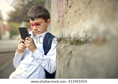 Young kid using his smartphone - stock photo