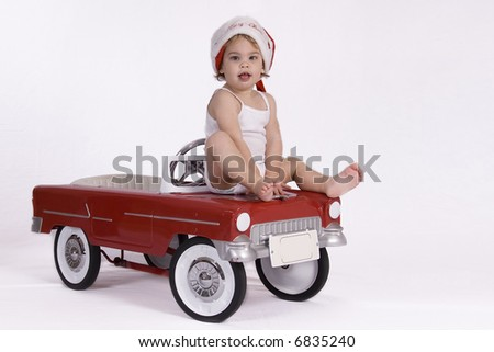 Young kid with Christmas hat sitting on a red car