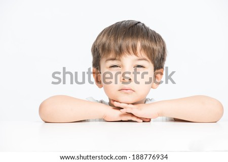 Young kid with narrowed eyes trying to do yoga, close up shot - stock photo